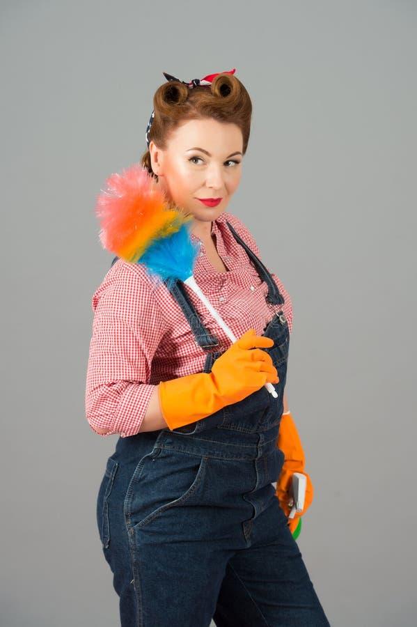 Donna delle pulizie con lo spolveratore colorato e guanti arancio del lattice nello stile di pin-up Retro governante disegnata de immagine stock libera da diritti