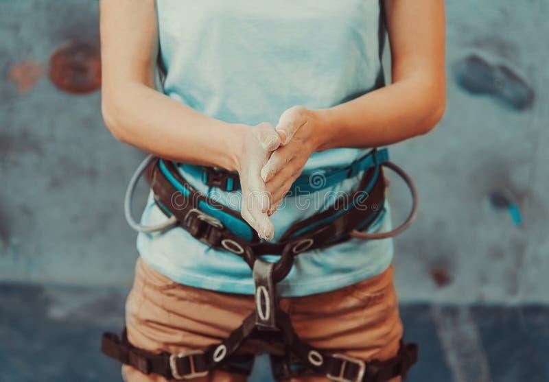 Donna dello scalatore che ricopre le sue mani nella polvere fotografia stock