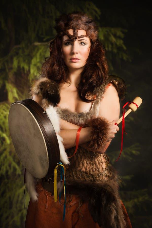 Donna dello sciamano con un tamburino nella foresta fotografia stock