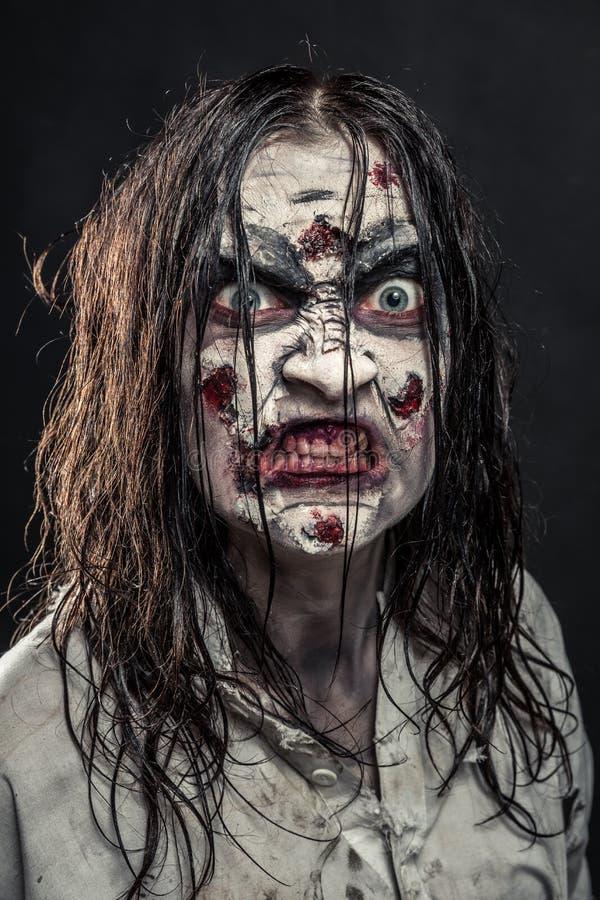 Donna dello zombie con il fronte sanguinoso fotografie stock libere da diritti