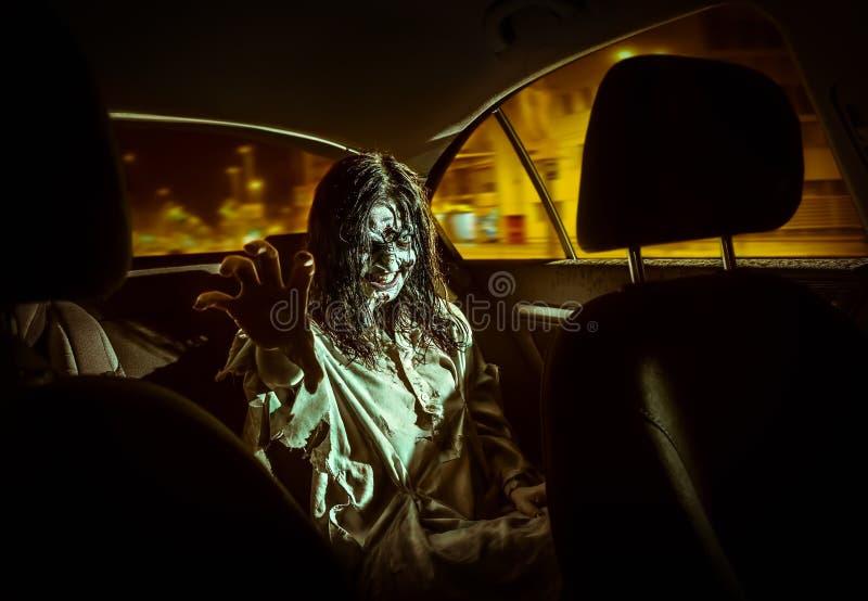 Donna dello zombie di orrore con il fronte sanguinoso nell'automobile immagine stock libera da diritti