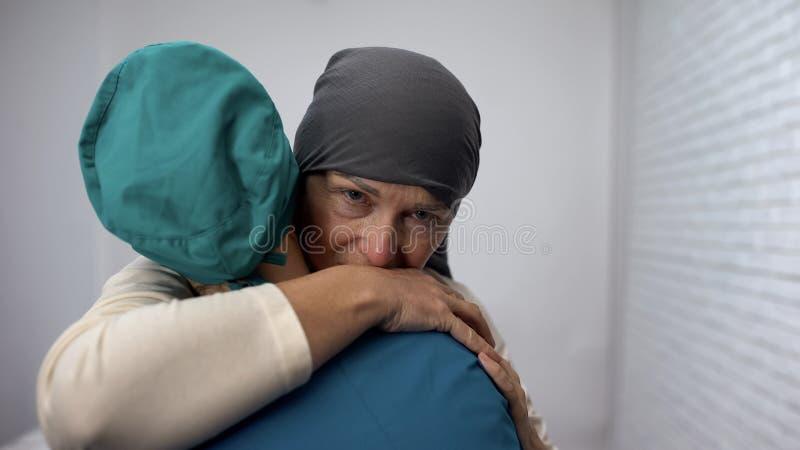 Donna depressa che grida e che abbraccia trattamento costoso dell'oncologo, chemioterapia immagini stock libere da diritti