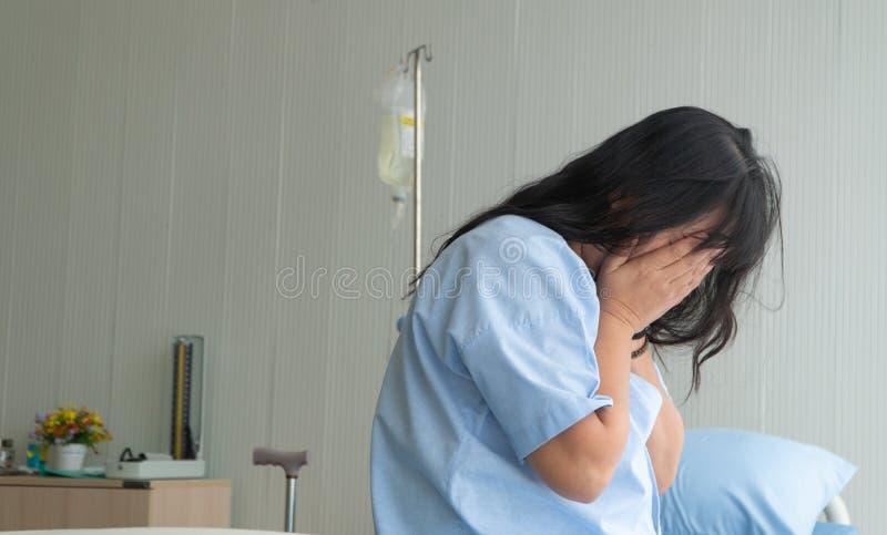 Donna depressa che si siede da solo sul letto paziente all'ospedale Fa soffrire sembrare negativa e preoccupata per la sue cattiv fotografia stock libera da diritti