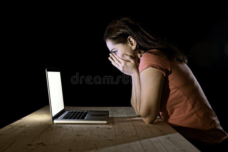 Donna depressa dello studente o del lavoratore che lavora con a tarda notte solo del computer nello sforzo fotografie stock libere da diritti