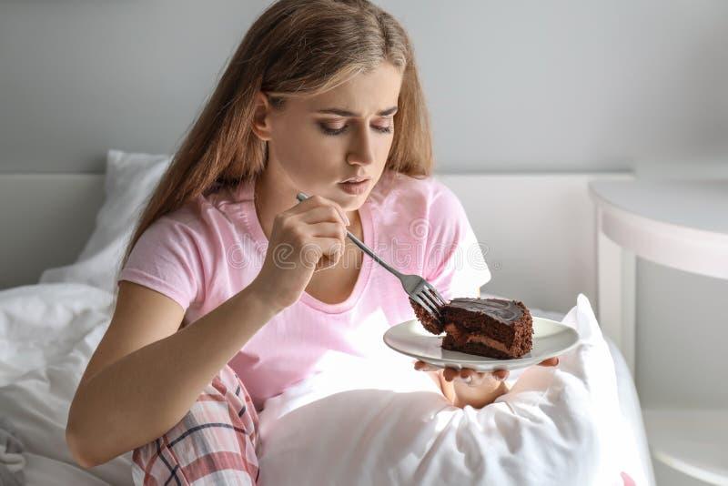 Donna depressa sola che mangia il dolce di cioccolato a casa fotografie stock
