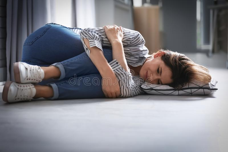 Donna depressa sola che si trova sul pavimento fotografie stock