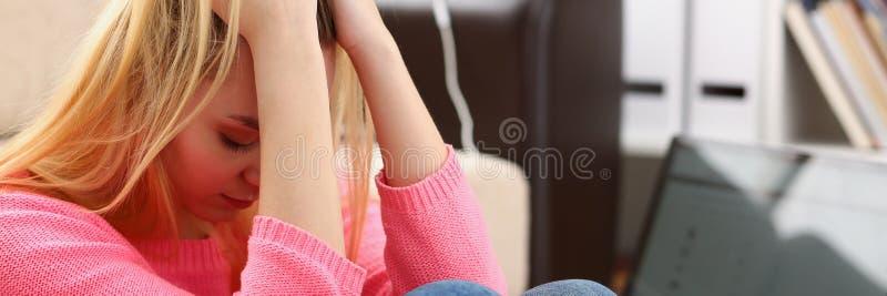 Donna depressa sola infelice che si siede sullo strato immagini stock libere da diritti