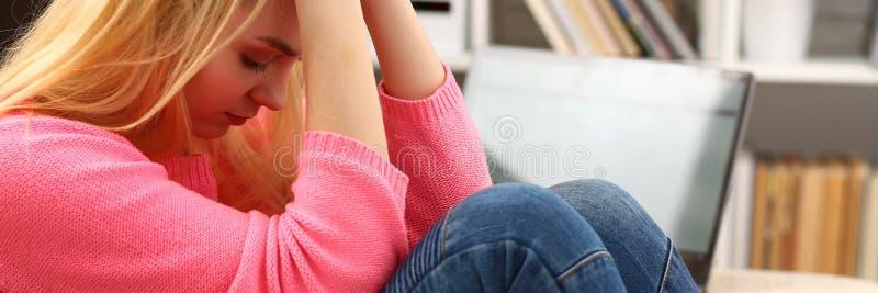Donna depressa sola infelice che si siede sullo strato fotografia stock