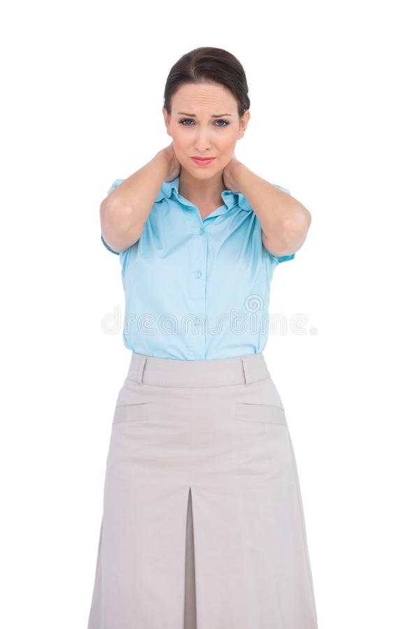 Donna di affari abbastanza giovane che soffre dal collo doloroso fotografie stock