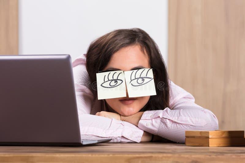 Donna di affari addormentata Covering His Eyes con le note appiccicose fotografia stock