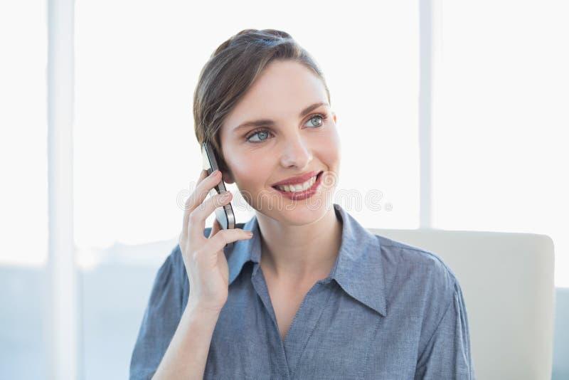 Donna di affari adorabile contenta che telefona con il suo smartphone che si siede al suo scrittorio immagine stock