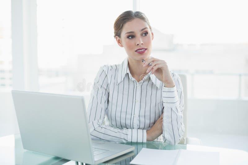 Donna di affari adorabile premurosa che si siede al suo scrittorio che tiene una matita fotografie stock libere da diritti