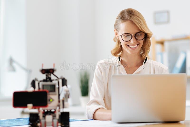 Donna di affari affascinante che gode della cooperazione con il robot all'interno fotografie stock