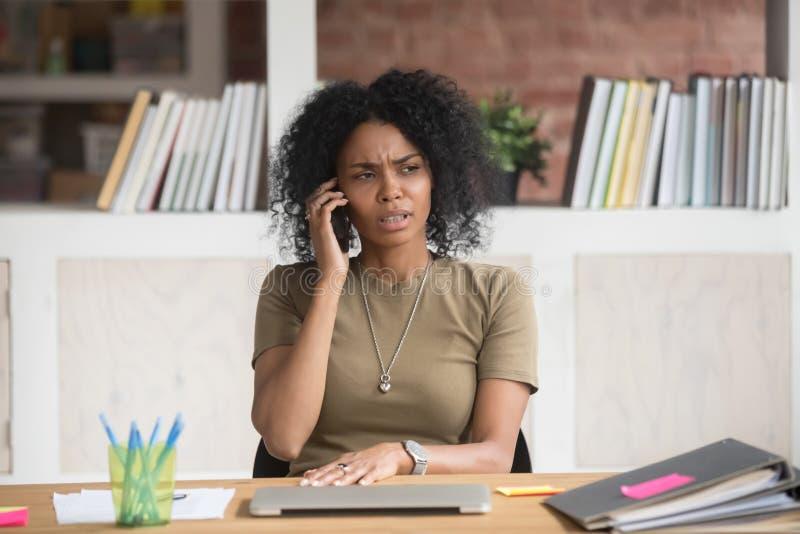 Donna di affari africana aggrottante le sopracciglia che ha conversazione sgradevole sul telefono fotografia stock
