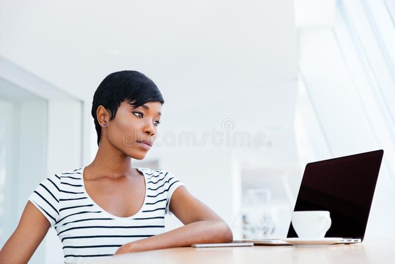 Donna di affari africana attraente seria che lavora con il computer portatile ed il caffè bevente fotografie stock libere da diritti