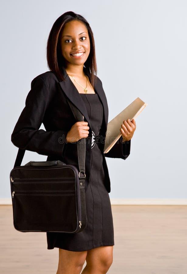 Donna di affari africana con la cartella immagini stock