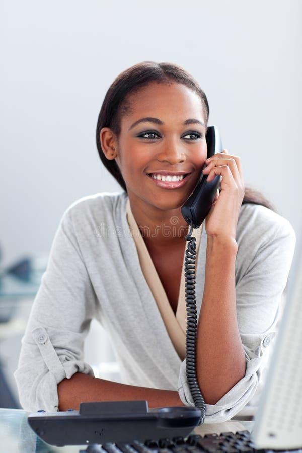 Donna di affari Afro-american che comunica su un telefono fotografia stock libera da diritti