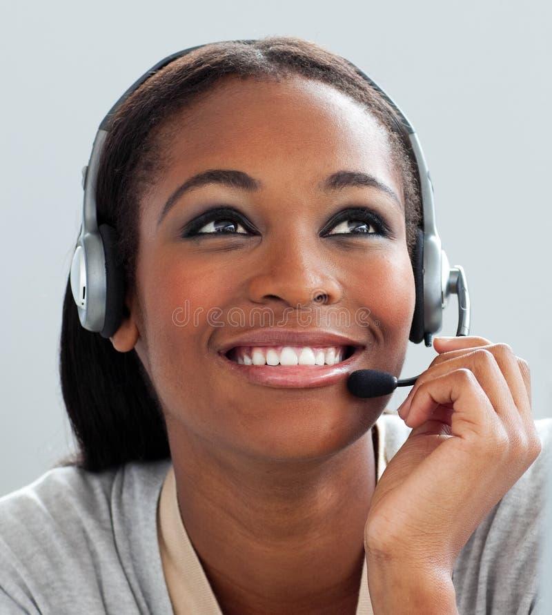 Donna di affari Afro-American che per mezzo della cuffia avricolare immagine stock