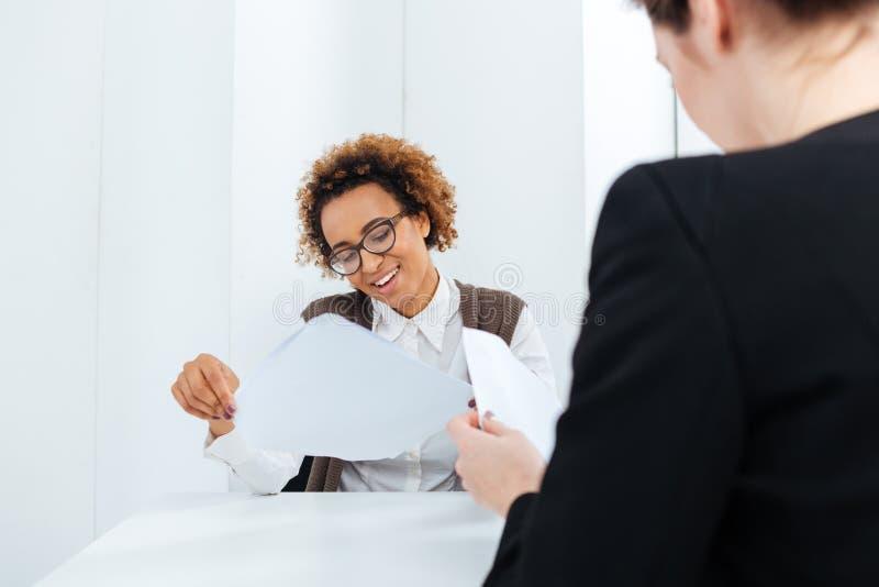 Donna di affari afroamericana sorridente che ha applicazione di riempimento e di intervista di lavoro fotografie stock libere da diritti