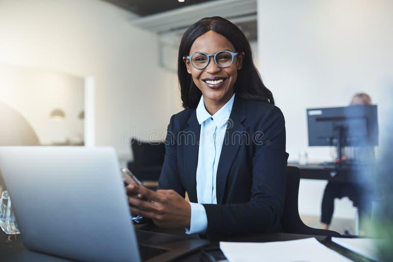Donna di affari afroamericana sorridente che per mezzo di un cellulare lei immagine stock