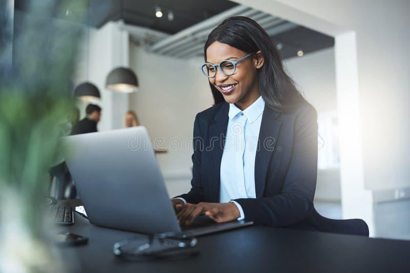 Donna di affari afroamericana sorridente che per mezzo di un computer portatile al suo DES immagine stock