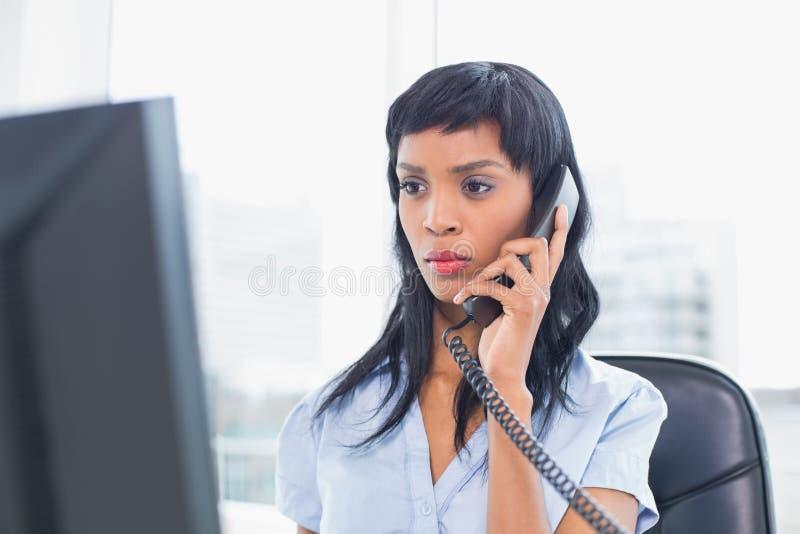 Donna di affari aggrottante le sopracciglia che risponde al telefono immagini stock