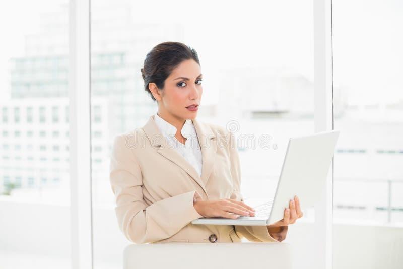 Donna di affari aggrottante le sopracciglia che sta dietro il suo computer portatile della tenuta della sedia fotografia stock