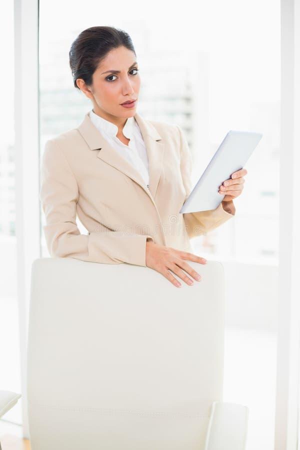 Donna di affari aggrottante le sopracciglia che sta dietro la sua compressa della tenuta della sedia fotografie stock libere da diritti