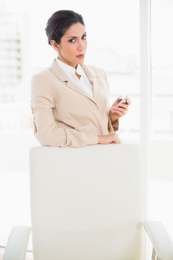 Donna di affari aggrottante le sopracciglia che sta dietro la sua sedia che tiene il suo telefono che abbaglia alla macchina fotog immagine stock libera da diritti