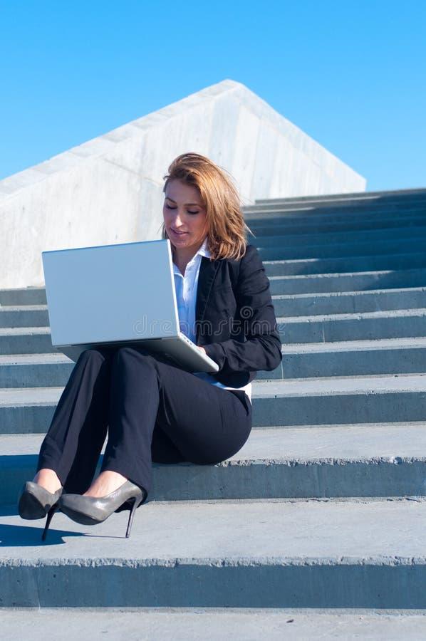 Donna di affari all'esterno con il computer portatile fotografia stock