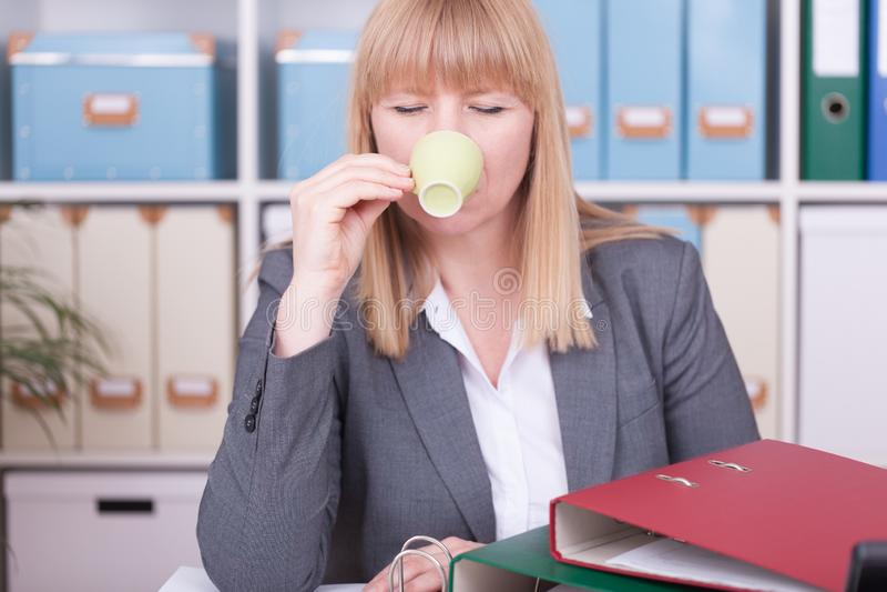 Donna di affari all'ufficio che beve una tazza di caffè fotografie stock