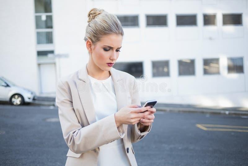 Donna di affari alla moda aggrottante le sopracciglia che invia un testo fotografia stock