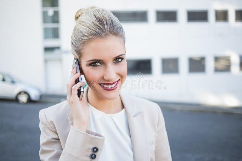 Donna di affari alla moda allegra che ha una telefonata fotografia stock