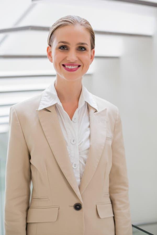 Donna di affari alla moda allegra che sta accanto alle scale fotografia stock libera da diritti