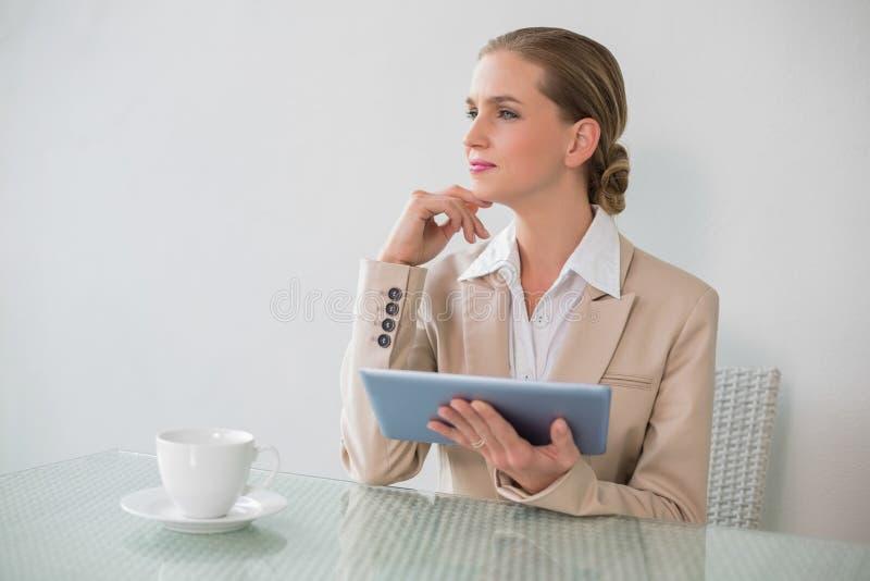 Donna di affari alla moda premurosa che per mezzo della compressa immagini stock