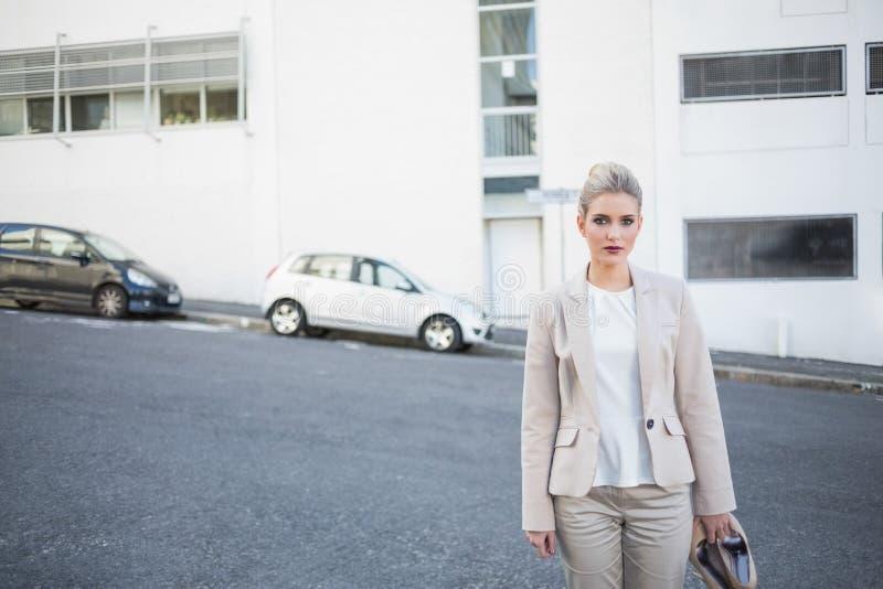 Donna di affari alla moda seria che tiene le sue scarpe fotografia stock