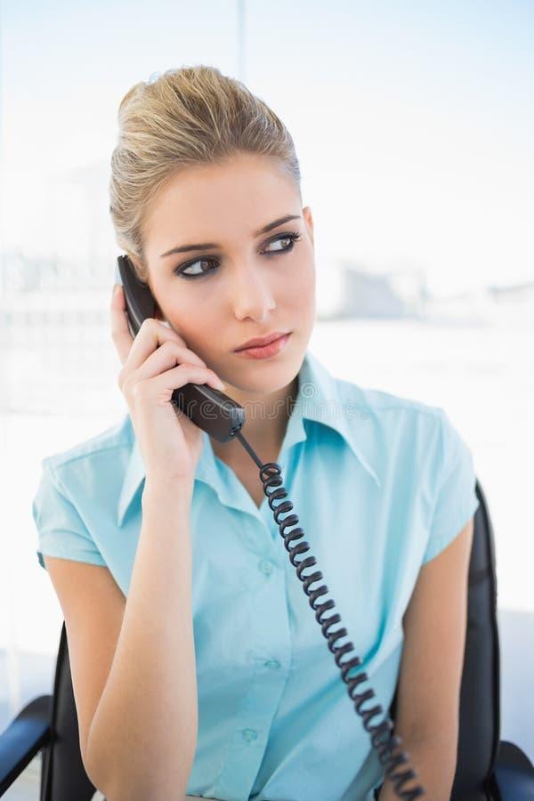Donna di affari alla moda seria sul telefono immagine stock