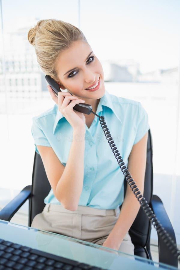 Donna di affari alla moda sorridente che risponde al telefono fotografie stock