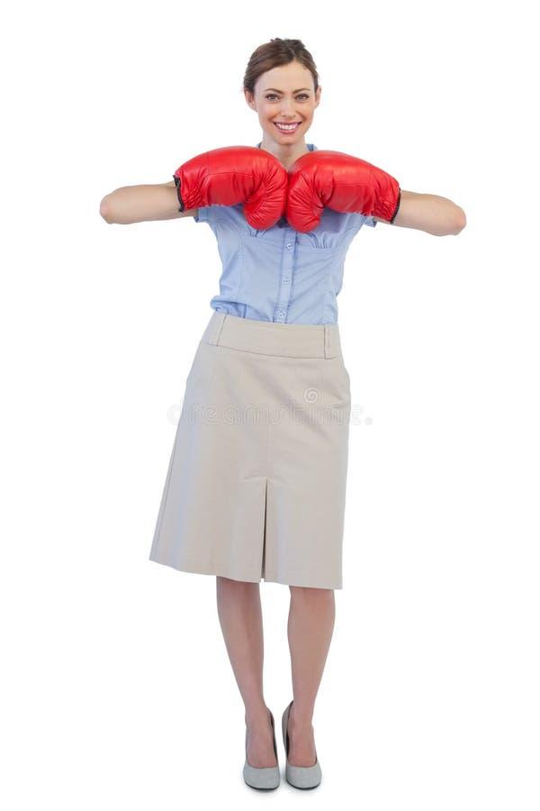 Donna di affari allegra che posa con i guantoni da pugile rossi fotografia stock libera da diritti