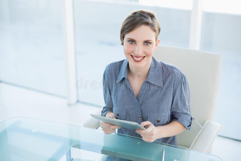 Donna di affari allegra che tiene la sua compressa che si siede al suo scrittorio fotografie stock libere da diritti