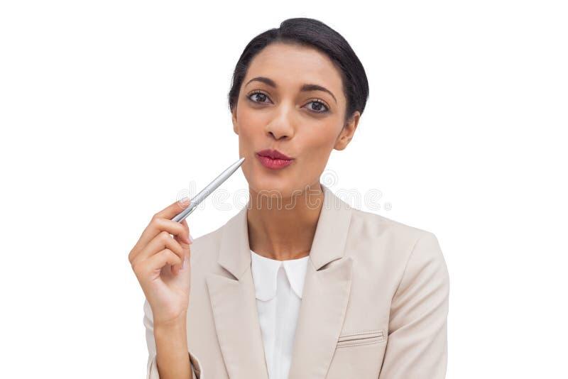 Donna di affari allegra che tiene una penna fotografia stock