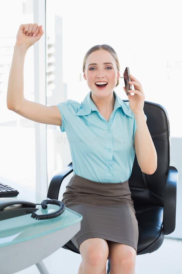 Donna di affari allegra di classe sul telefono che incoraggia con le armi alzate immagine stock
