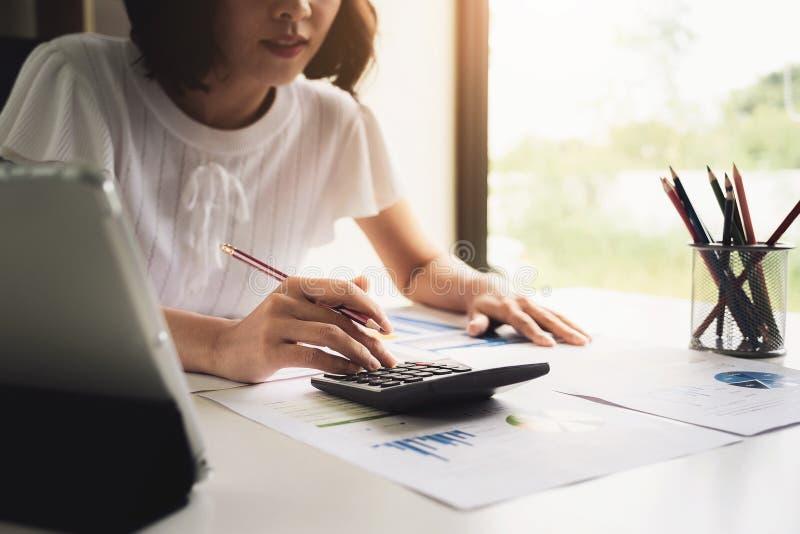 Donna di affari alta vicina facendo uso del calcolatore e del computer portatile per fare finanza di per la matematica sullo scri fotografia stock