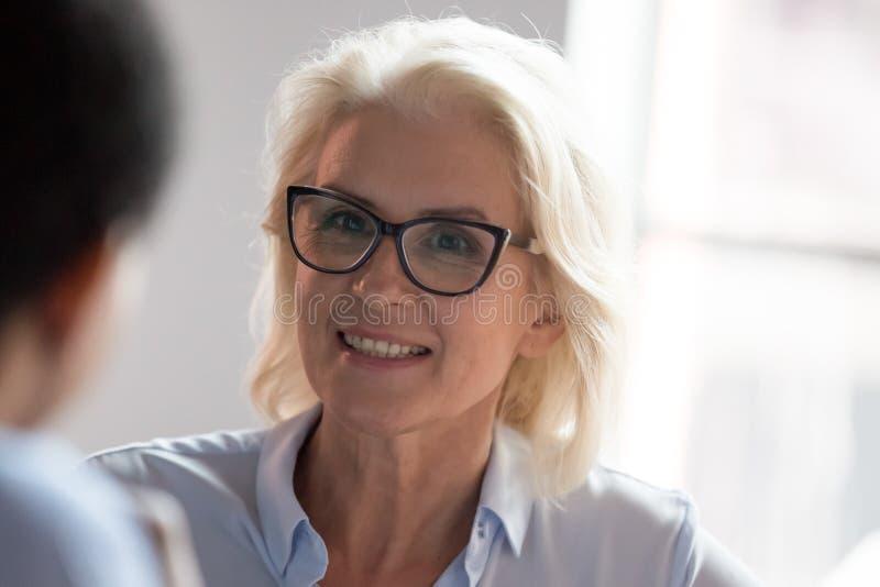 Donna di affari anziana sorridente che esamina il cliente d'ascolto del collega incontrarsi fotografie stock