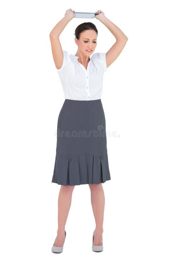 Donna di affari arrabbiata che getta il suo pc della compressa fotografia stock libera da diritti