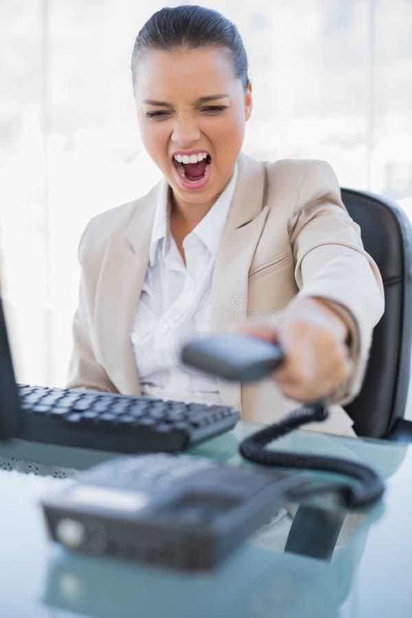 Donna di affari arrabbiata che grida mentre appendendo sul telefono fotografia stock