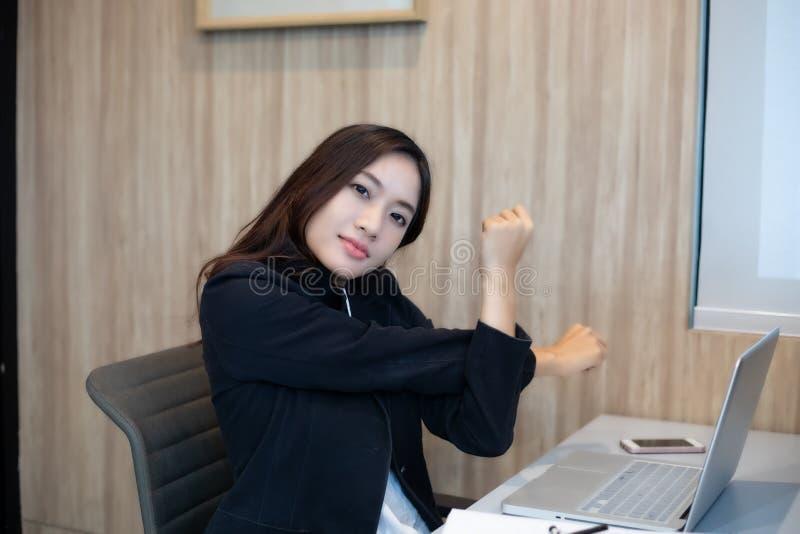 Donna di affari asiatica che allunga duro dopo il lavoro nell'ufficio fotografia stock libera da diritti