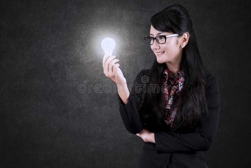Donna di affari asiatica che esamina una lampadina luminosa fotografie stock