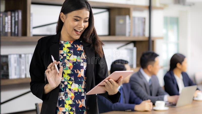 Donna di affari asiatica che lavora con la compressa astuta immagini stock libere da diritti