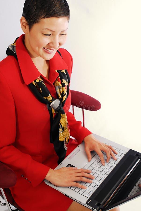 Donna di affari asiatica con il computer portatile fotografia stock libera da diritti